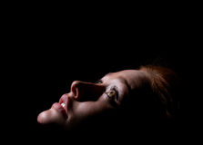 La muchacha mira para arriba en oscuridad Imagenes de archivo