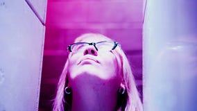 La muchacha mira para arriba Su cara es iluminada por una luz multicolora almacen de metraje de vídeo