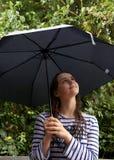 La muchacha mira para arriba su paraguas imagen de archivo