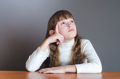 La muchacha mira para arriba y piensa Imagen de archivo