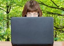 La muchacha mira sobre la cubierta del ordenador portátil y del bosque verde Imagenes de archivo