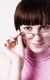 La muchacha mira sobre los vidrios Fotos de archivo