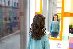 La muchacha mira su pelo encrespado en el espejo Imagenes de archivo