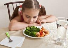 La muchacha mira tranquilamente el plato con la carne y el bróculi Imagen de archivo
