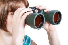 La muchacha mira a través de los vidrios de campo aislados en blanco Fotos de archivo libres de regalías