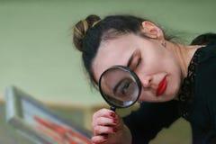 La muchacha mira a través de una lupa foto de archivo libre de regalías