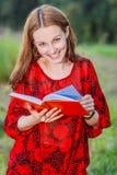 La muchacha mira a través del diario semanal Fotos de archivo