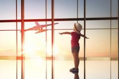 La muchacha mira un avión el aeropuerto fotos de archivo