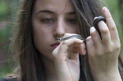 La muchacha mira una serpiente Fotografía de archivo libre de regalías