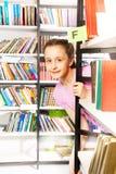 La muchacha mira y se coloca detrás del estante en biblioteca Foto de archivo libre de regalías