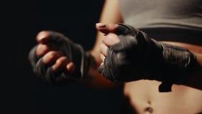 La muchacha misma que venda sus manos con los vendajes antes del combate en un fondo negro Prepárese para la batalla Primer almacen de metraje de vídeo