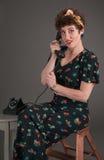 La muchacha modela en equipo florecido en el teléfono parece sorprendida Fotos de archivo libres de regalías