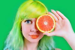 La muchacha modelo hermosa con el peinado colorido toma el jugo rojo en fondo verde Fotografía de archivo libre de regalías
