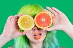 La muchacha modelo hermosa con el peinado colorido toma el jugo rojo y amarillo en fondo verde Fotografía de archivo