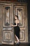 La muchacha modelo morena atractiva con un corte de pelo de moda y con maquillaje brillante, en un vestido largo negro de moda, s fotos de archivo libres de regalías