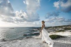 La muchacha modelo rubia joven hermosa, en el vestido blanco, se coloca media de lado en la costa y mira el mar foto de archivo