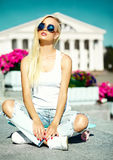 La muchacha modelo rubia joven hermosa en inconformista del verano viste con el monopatín Foto de archivo