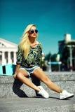La muchacha modelo rubia joven hermosa en inconformista del verano viste con el monopatín Imágenes de archivo libres de regalías