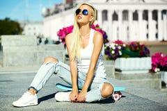 La muchacha modelo rubia joven hermosa en inconformista del verano viste con el monopatín Imagenes de archivo