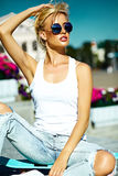 La muchacha modelo rubia joven hermosa en inconformista del verano viste con el monopatín Fotos de archivo libres de regalías