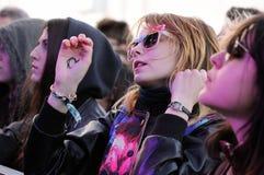 La muchacha moderna rubia con las gafas de sol rosadas extravagantes y un corazón dibujado en su mano, miran un concierto en el so Fotografía de archivo libre de regalías