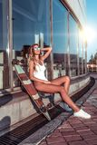 La muchacha moderna y hermosa toma el sol la ciudad del verano, cerca de las ventanas de cristal, el traje de baño blanco del cue imagen de archivo libre de regalías