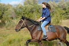 La muchacha monta a caballo imagen de archivo