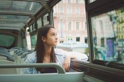 la muchacha monta en el bus turístico y mira hacia fuera la ventana St Petersburg, Rusia imagen de archivo libre de regalías