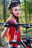 La muchacha monta la bicicleta en hierba verde en el parque al aire libre Foto de archivo