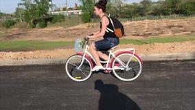 La muchacha monta una bici en una carretera de asfalto Detr?s de su mochila, en una cesta del cargo al manojo de flores almacen de video