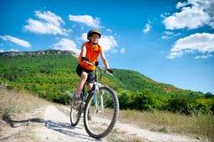 La muchacha monta una bicicleta Imagen de archivo libre de regalías