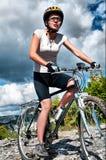 La muchacha monta una bicicleta Fotos de archivo libres de regalías