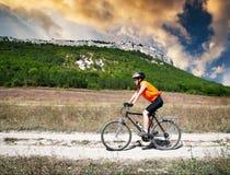 La muchacha monta una bicicleta Fotografía de archivo libre de regalías