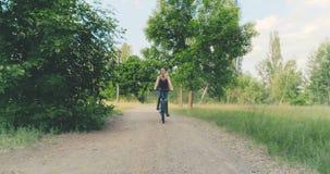 La muchacha monta una bicicleta en el campo almacen de metraje de vídeo