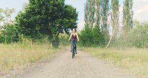 La muchacha monta una bicicleta en el campo metrajes