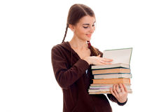 La muchacha morena alegre elegante del estudiante con las coletas en deportes marrones viste con los libros en su presentación de Foto de archivo libre de regalías