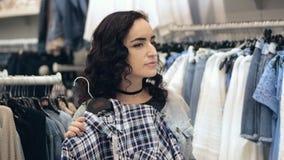 La muchacha morena atractiva elige miradas del vestido en espejo La morenita hermosa de la mujer compra ropa en tienda Señora bon metrajes