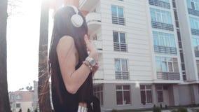 La muchacha morena atractiva en una blusa negra que disfruta de la música en una sol brillante, baila y canta adelante emocionalm almacen de metraje de vídeo