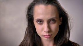 La muchacha morena atractiva joven es baile, jugando con el pelo, labio penetrante, concepto del ligón, fondo gris metrajes