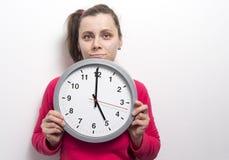 La muchacha morena caucásica joven con mueca en su cara se sostiene alrededor del reloj contra el fondo blanco de la pared Foto de archivo libre de regalías