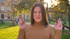 La muchacha morena caucásica joven cruza sus fingeres en esperanza feliz en fondo verde del parque almacen de video