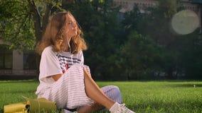 La muchacha morena caucásica joven se sienta en un parque en la hierba y escucha la música en los auriculares en un smartphone almacen de video