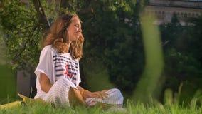 La muchacha morena caucásica joven se sienta en un parque en la hierba y escucha la música en los auriculares en un smartphone, s metrajes