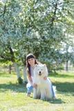 La muchacha morena con un perro blanco grande Fotos de archivo libres de regalías