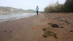 la muchacha morena corre lejos en la playa contra la isla almacen de metraje de vídeo