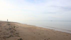 la muchacha morena corre más allá en la playa contra el barco en el amanecer