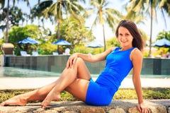 la muchacha morena en azul se sienta en la barrera de piedra contra piscina Fotos de archivo