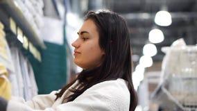 La muchacha morena en una tienda de la materia textil elige la toalla metrajes
