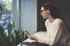 La muchacha morena en vidrios realiza charla en línea del trabajo diario con los empleados que controlan el trabajo de la compañí Foto de archivo libre de regalías