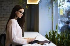 La muchacha morena en vidrios realiza el libro electrónico del trabajo diario en la lección de la literatura que piensa en coment Imagenes de archivo